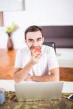 Pomme mangeuse d'hommes belle et travail avec l'ordinateur portable à la cuisine à la maison photos libres de droits