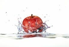 Pomme rouge éclaboussant dans l'eau. Photographie stock