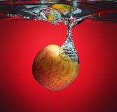 Pomme rouge éclaboussant dans l'eau Photographie stock libre de droits