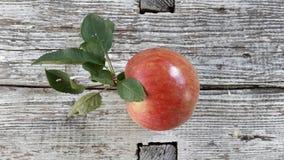 Pomme rouge avec des feuilles sur la vieille surface en bois photos stock