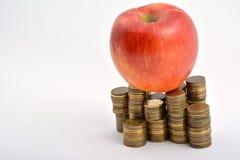 Pomme rouge avec des pièces de monnaie d'isolement sur le blanc Photographie stock libre de droits