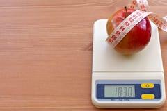 Pomme rouge avec la bande de mesure sur l'échelle électronique, d Photos stock