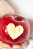 Pomme rouge avec un coupe-circuit en forme de coeur Photos libres de droits