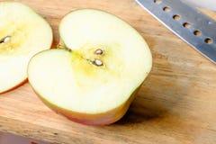 Pomme rouge de Halfs sur en bois Photos stock