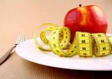 Pomme rouge de la plaque blanche avec le ruban métrique, le couteau et la fourchette Photographie stock libre de droits