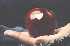 Pomme rouge fraîche avec un coupe-circuit en forme de coeur chez la main de la femme sur le repaire Images stock