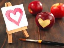 Pomme rouge fraîche avec un découpage en forme de coeur et un coeur peint Photos stock