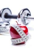 Pomme rouge fraîche, ruban métrique, et dans les haltères de forme physique de fond Images libres de droits