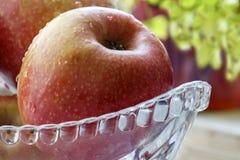 Pomme rouge mûre dans une rosée dans un bol en verre Photo stock