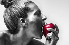 Pomme rouge mordante de femme Photographie stock libre de droits