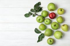 Pomme rouge parmi la verte et espace pour le texte sur le fond en bois, vue supérieure images libres de droits
