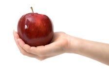 Pomme rouge savoureuse chez la main de la femme sur le blanc, d'isolement Photo stock