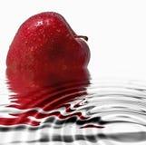 Pomme rouge se reflétant dans l'eau Images libres de droits