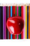 Pomme rouge sur des crayons de couleur Photographie stock libre de droits