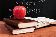 Pomme rouge sur les livres et le tableau noir d'école avec des équations mathématiques dans la salle de classe Photo stock