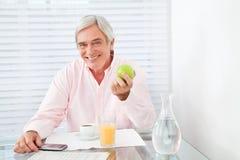 Pomme saine de fixation d'homme aîné Photographie stock