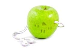 Pomme verte avec des écouteurs photographie stock libre de droits