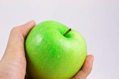 Pomme verte avec des mains Photographie stock