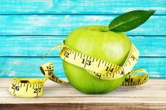 Pomme verte avec la bande de mesure d'isolement sur en bois Image libre de droits