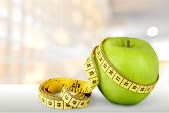 Pomme verte avec la bande de mesure sur en bois Photo libre de droits
