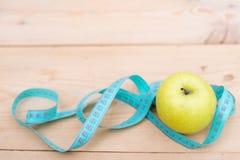 Pomme verte avec la bande de mesure sur le fond en bois Suivez un régime le concept Place pour le texte photos libres de droits