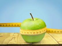 Pomme verte avec la bande de mesure sur la table Photos stock