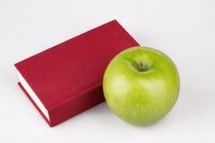 Pomme verte avec le livre rouge sur le blanc Photographie stock