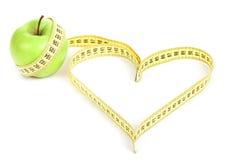 Pomme verte avec un symbole de mesure de bande et de coeur  Images libres de droits