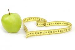 Pomme verte avec un symbole de mesure de bande et de coeur d'isolement Images stock