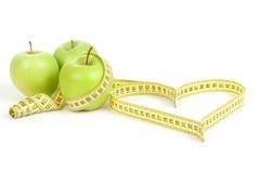 Pomme verte avec un symbole de mesure de bande et de coeur d'isolement Image stock