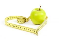 Pomme verte avec un symbole de mesure de bande et de coeur d'isolement Photo stock