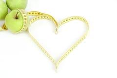 Pomme verte avec un symbole de mesure de bande et de coeur d'isolement Photographie stock