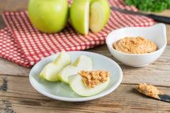 Pomme verte coupée en tranches avec le beurre d'arachide image stock