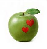 Pomme verte d'isolement avec deux coeurs Photos stock