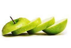 Pomme verte dans les parts d'isolement sur le blanc Photographie stock