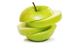 Pomme verte dans les parts d'isolement sur le blanc Photo libre de droits