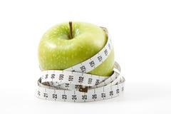 Pomme verte et bande de mesure Photos stock