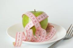Pomme verte et bande de mesure d'une plaque blanche Photographie stock