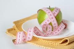 Pomme verte et bande de mesure d'une plaque blanche Images stock