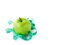 Pomme verte et bande de mesure sur le fond blanc Images libres de droits