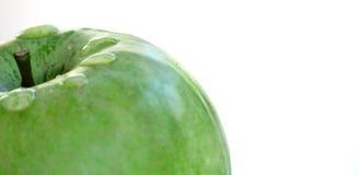 Pomme verte mûre sur un fond blanc avec des gouttes de l'eau après pluie photos libres de droits