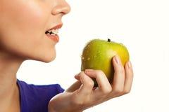 Pomme verte mordante de femme Photos stock