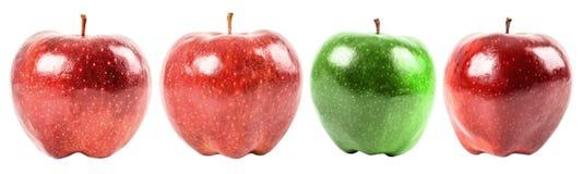 Pomme verte parmi les pommes rouges Images stock