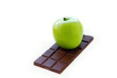 Pomme verte se trouvant sur le bar de chocolat Image libre de droits