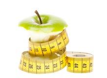 Pomme verte suivante un régime de concept avec la bande de mesure Photographie stock