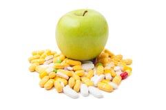 Pomme verte sur des pilules Photos libres de droits