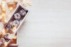 Pommes argentées et lumières de Noël brûlant dans des boîtes sur un fond blanc en bois Photographie stock libre de droits