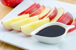 Pommes avec du chocolat sur la table en bois Images stock
