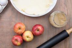Pommes avec la compote de pommes à côté d'une pâte pour faire une tarte aux pommes Photographie stock libre de droits