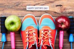 Pommes, chaussures en caoutchouc et corde de saut Image stock